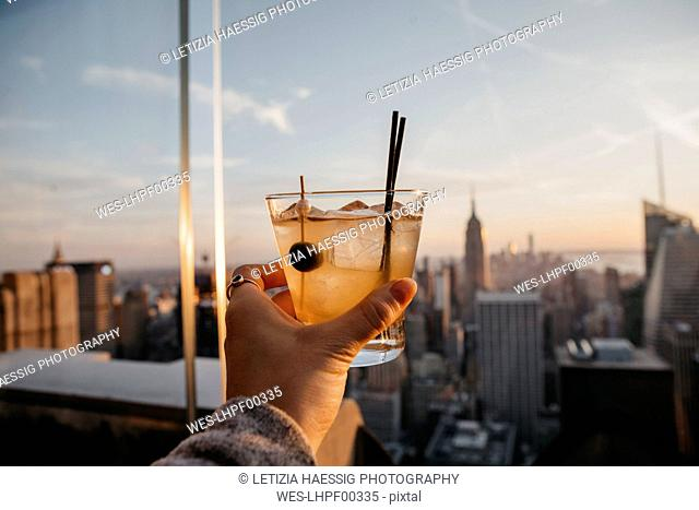 USA, New York, New York City, hand with cocktail glass at sunrise