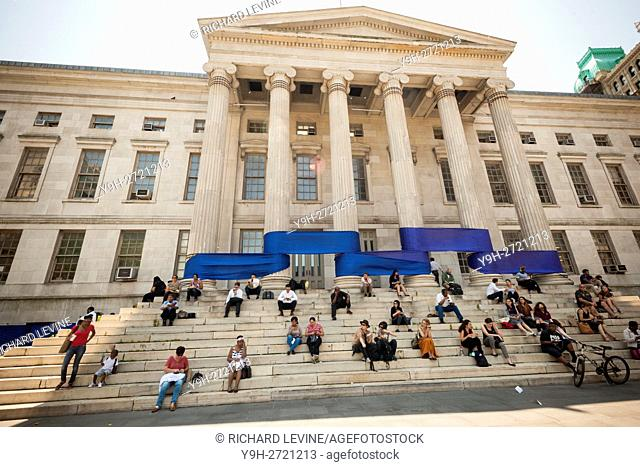 Office workers on their lunch hour sit on the steps of Brooklyn Borough Hall in the New York borough of Brooklyn in front of the blue part of a rainbow ribbon...