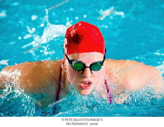 Teenage girl in red swimming cap and goggles swimming in pool