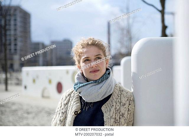 Young woman leaning against wall in playground, Munich, Bavaria, Germany