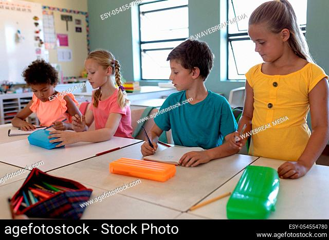 Front view of a diverse group of four schoolchildren sitting at desks writing in an elementary school classroom, one Caucasian girl with blonde hair and wearing...