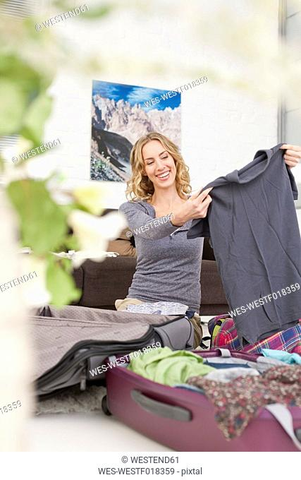 Germany, Leipzig, Mid adult woman packing suitcase, smiling