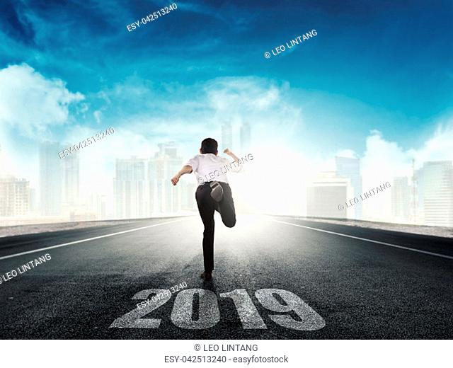 Rear view of asian businessman running to city with 2019 number on the street. Happy New Year 2019