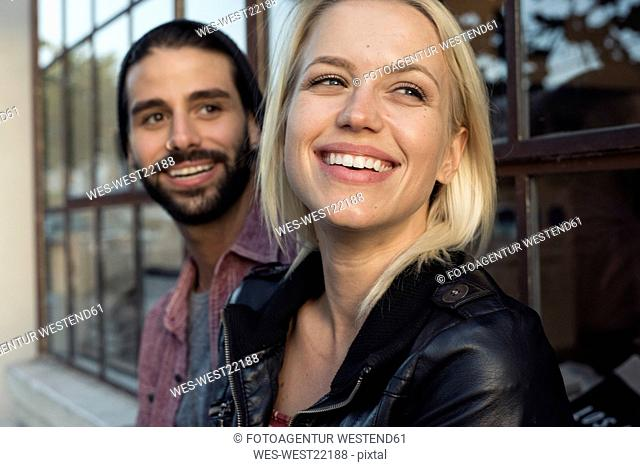 Happy young couple outdoors looking sideways