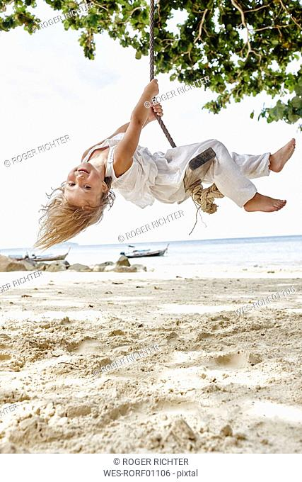 Thailand, Phi Phi Islands, Ko Phi Phi, happy little girl on a rope swing on the beach
