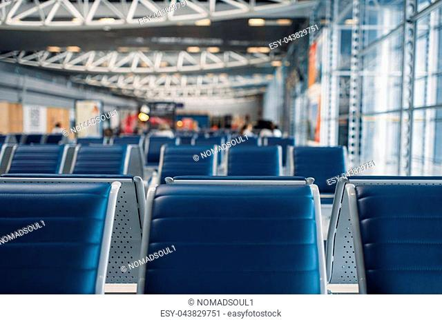 Row of seats in airport waiting zone, nobody. Departure area of air terminal, travelling concept, flight transportation