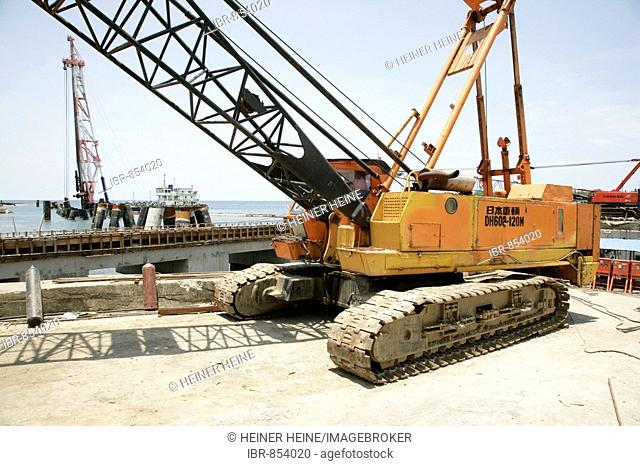 Crawler crane during the building of a refinery and harbour area for the Ramu Nickel Mine, chinese mining company, Basamuk, Papua New Guinea, Melanesia