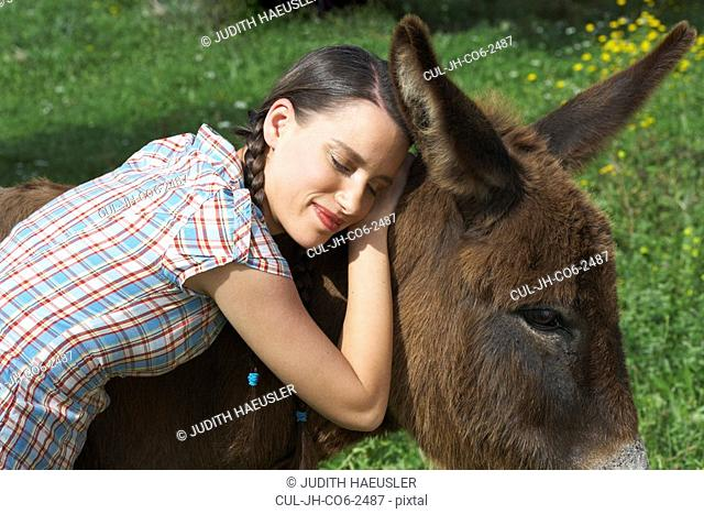 Young girl embracing donkey eyes closed portrait
