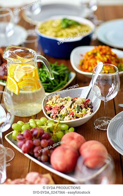salad, jug of water and other food on wooden table