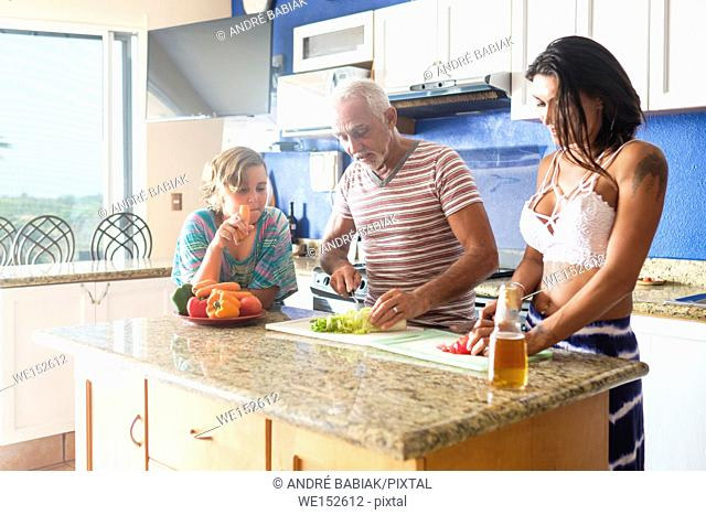 Older man cutting vegetables in the kitchen with young attractive woman, child watchin