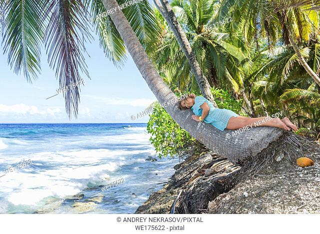 Relaxing woman lies on the coconut palm tree on a tropical beach. Young beautiful woman lying on the palm tree on sea shore