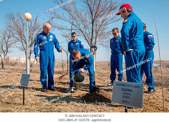 Behind their Cosmonaut Hotel crew quarters in Baikonur, Kazakhstan, Expedition 47-48 crewmember Alexey Ovchinin of Roscosmos (center) plants a tree in...