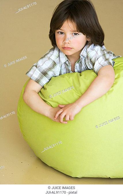 Preschool boy laying on bean bag