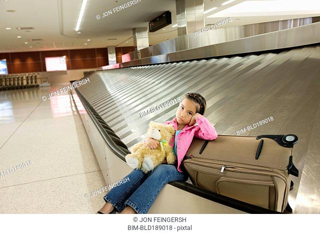 Tired Asian girl sitting on luggage carousel