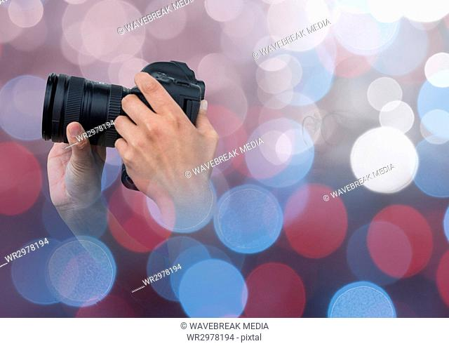 hands holding a camera against glowing background