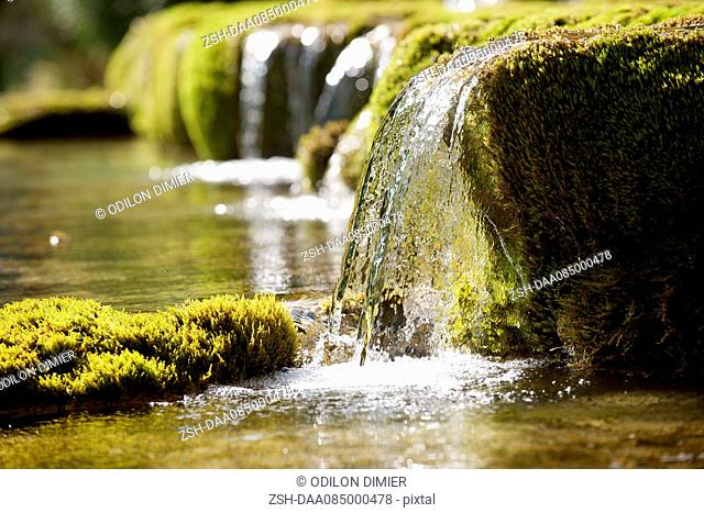 Water flowing over moss covered rocks