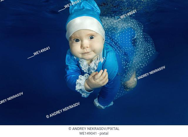 Little girl in Santa's blue suit swimming underwater in the pool