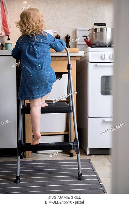 Caucasian girl climbing ladder in kitchen