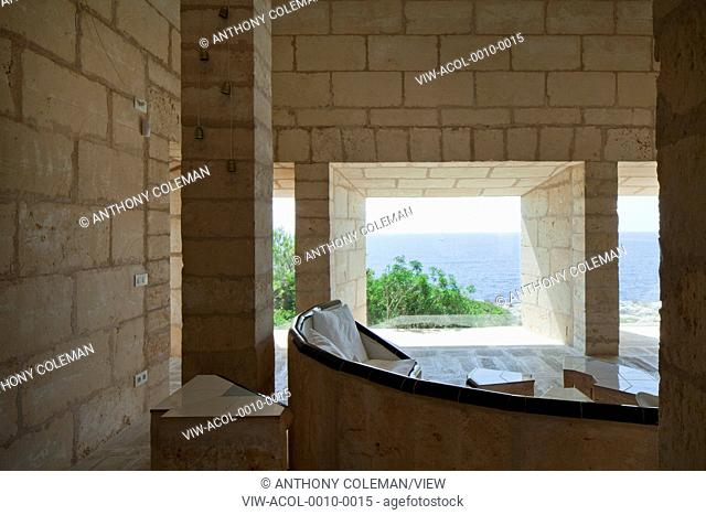 Can Lis, Mallorca, Spain. Architect: Utzon, Jorn, 1971. Living room with built in crescent shaped sandstone sofa and frameless windows