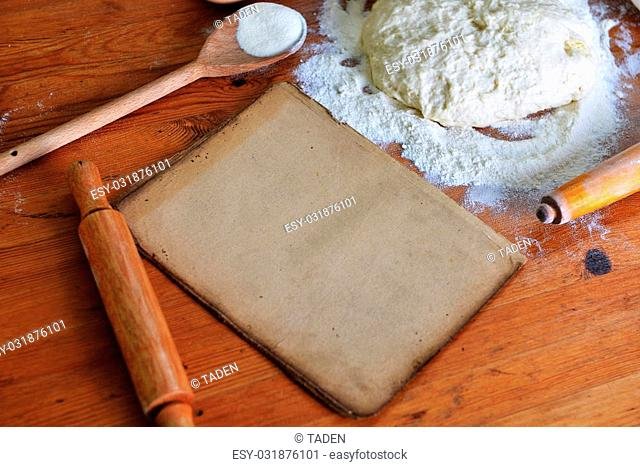 yeast dough, old sheet and flour on wooden background
