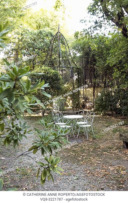 Elegant bell shaped metal canopy protects a stone well in a tree lined courtyard garden with decorative curlicue white cafe table and chairs in...