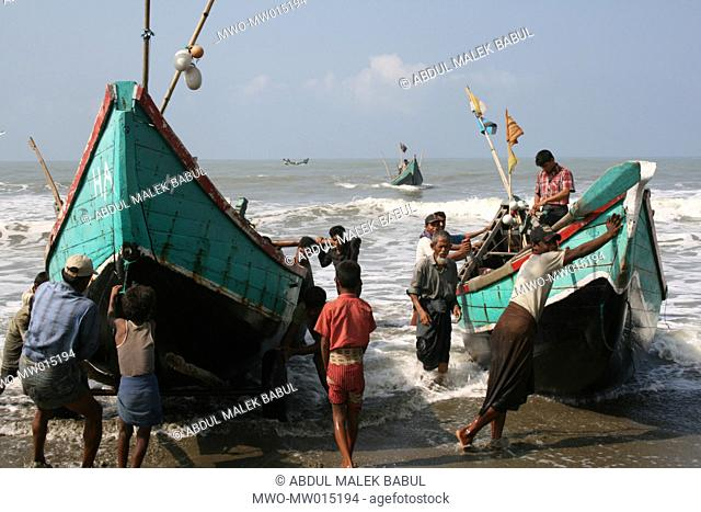 Fishermen bringing their boat to the shore, at Shah Porir Island, Teknaf, Cox's Bazar, Bangladesh March 22, 2008