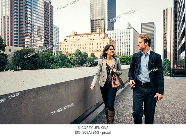 Businessman and woman walking and talking in city, Los Angeles, USA