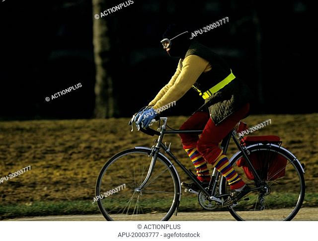 Man in colourful clothing riding a bicycle