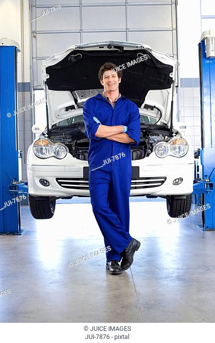 Male car mechanic, in blue overalls, standing in front of car with open bonnet on hydraulic platform in auto repair shop, smiling, front view, portrait