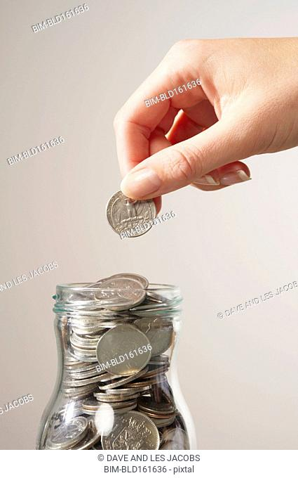 Caucasian woman saving coins in bottle