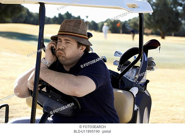 Bored man talking on phone in golf cart