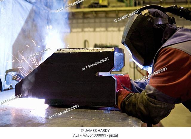 Coated textile plant, maintenance workshop, welder performing arc welding