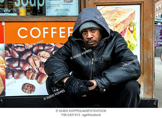 New York, USA. Homeless man of African American ethnicity, living in the streets of Manhattan, in front of a coffee shop