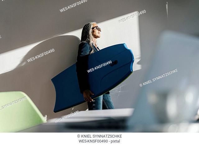 Businesswoman in office holding surboard enjoying sunlight