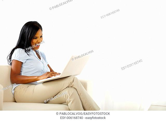 Portrait of a pretty young woman working on laptop and having fun