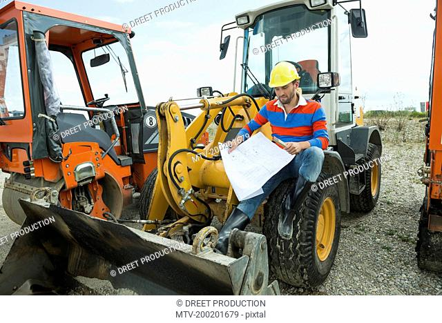 Construction worker sitting on excavator holding construction plan