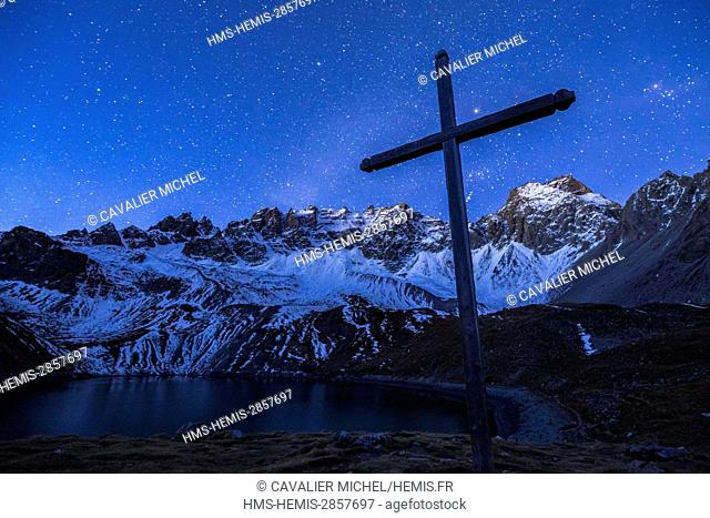 France, Hautes Alpes, regional natural reserve of Queyras, Ceillac, cross of the chapel saint Anne and the lake saint Anne (2415m) dominated by the Peaks of...