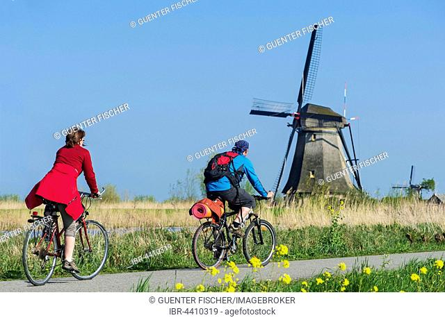 Two cyclists passing a windmill in Kinderdijk, The Netherlands