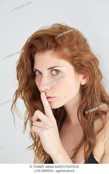 Young redhead woman with finger on her lips, looking at camera