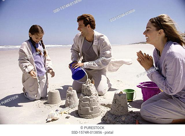 Parents and their daughter making a sand castle on the beach