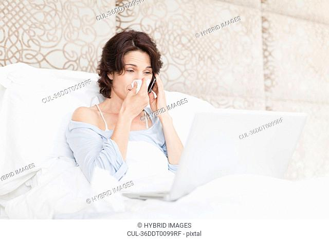 Woman blowing her nose in bed