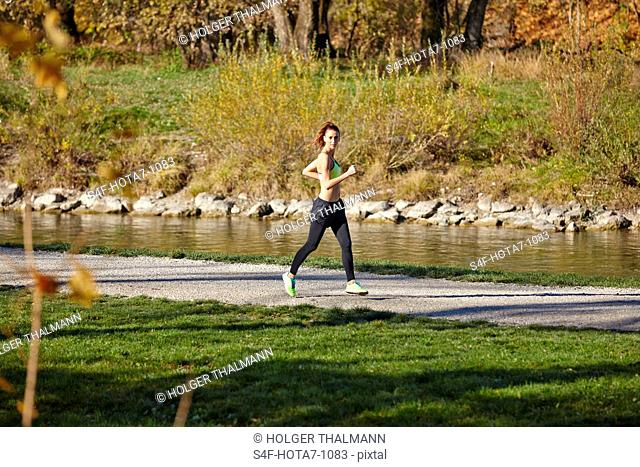 Frau joggt am Flussufer
