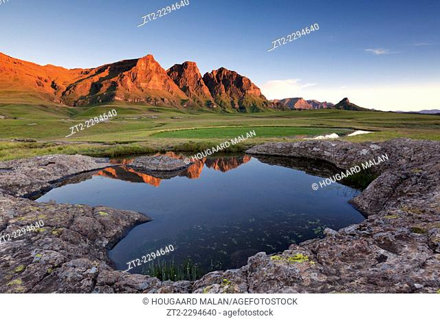 Landscape view of the Three Bushmen peaks reflected in a tarn pool at sunrise. Sehlabathebe National park, Lesotho