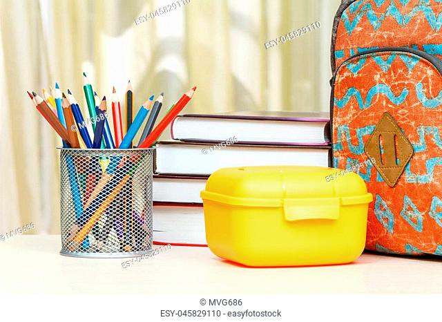 School backpack with school supplies. Books, metal stand for pencils with color pencils and yellow sandwich box on wooden table