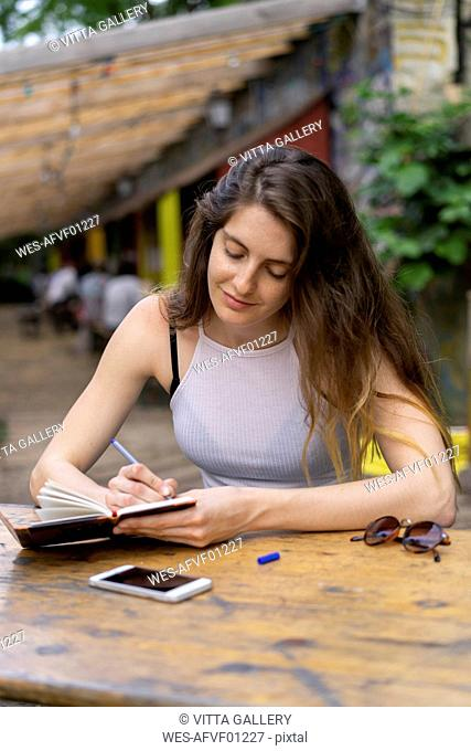 Young woman sitting at table taking notes