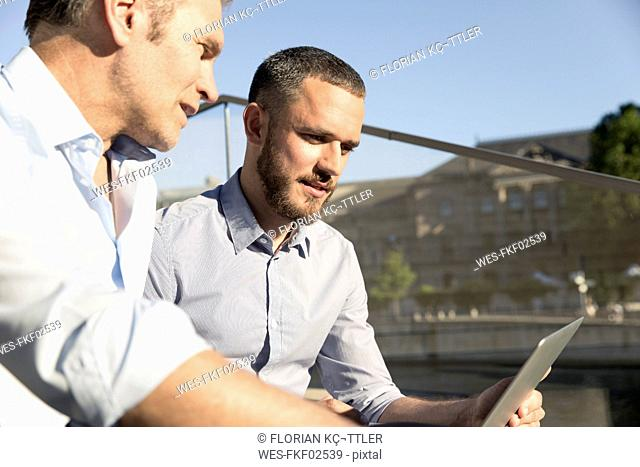 Two businessmen sitting on stairs using laptop