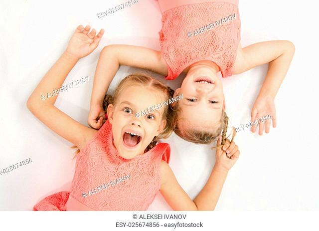 Two girls sisters in the same clothes lie on a white surface next to a head-to-head look at the picture and smiling