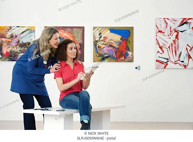 Mid adult woman advising art student drawing in sketch pad in art gallery