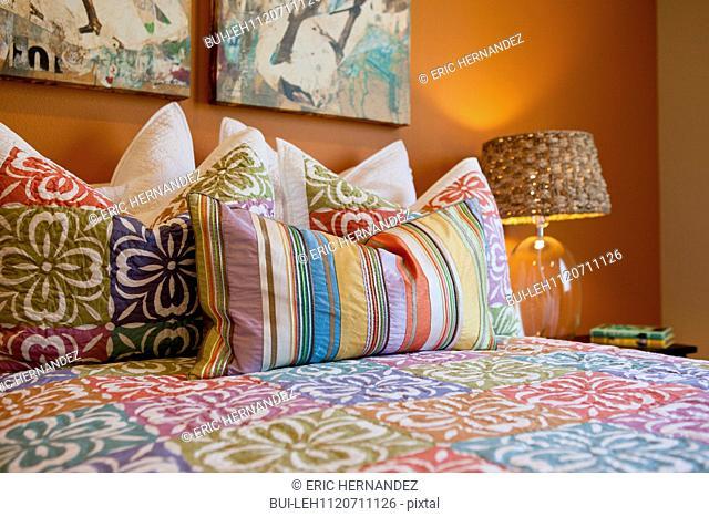 Throw pillows arranged on bed in house; Azusa; California; USA