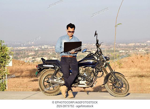 Young man sitting on bike working on laptop near mountain, Pune, Maharashtra